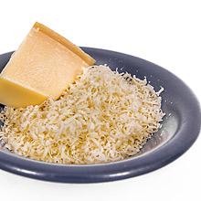 Parmesankäse, gerieben und am Stück auf einem blauen Teller