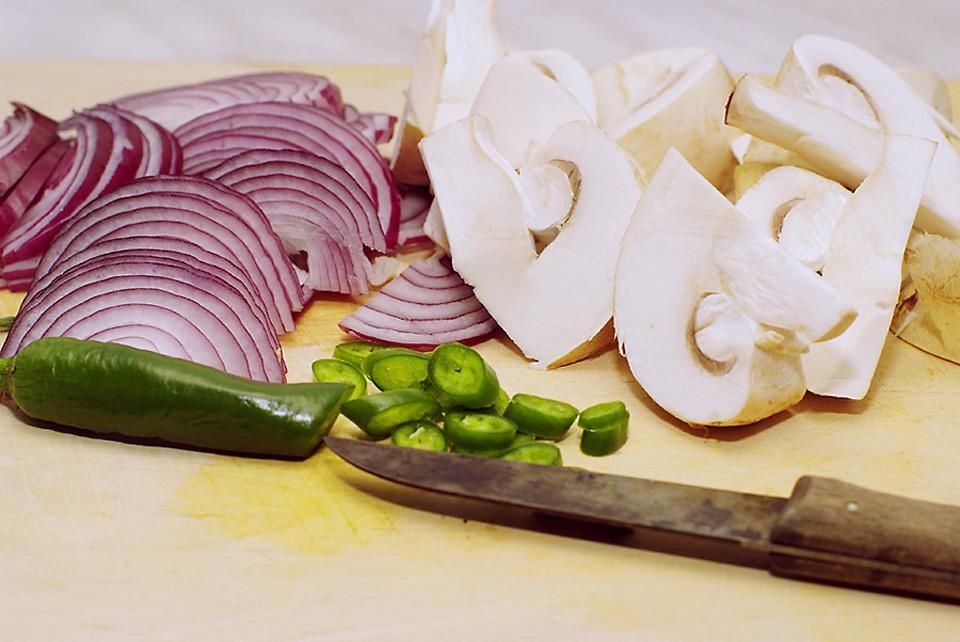 Zwiebeln, Pepperoni, Champignons und ein rostiges Küchenmesser